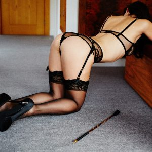 Kinky submissive escort Louisa Knight bends over with riding crop