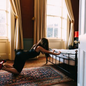 Submissive escort Louisa Knight in a black dress and Christian Louboutins bent over a bed