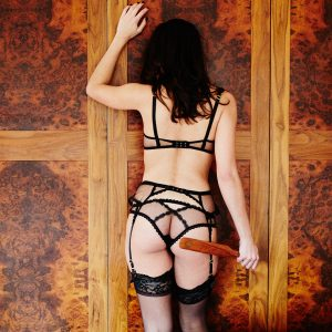Kinky escort Louisa Knight with wooden spanking pandle