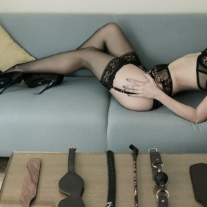Escort Louisa Knight poses in lingerie with BDSM implements - paddles, blindfolds, collars and gags