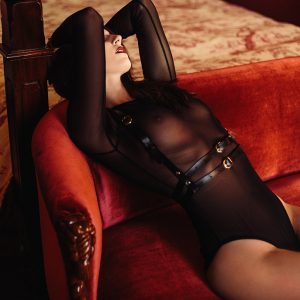 Kinky submissive Louisa Knight in a leather harness and bodysuit reclining