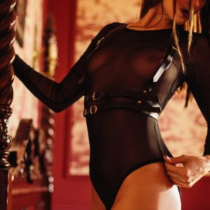 Kinky submissive Louisa Knight in a leather harness and bodysuit sat on a bed