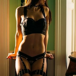 submissive escort Louisa Knight in black kinky bordelle harness lingerie and collar