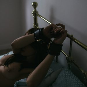 Submissive escort Louisa Knight in bondage cuffs