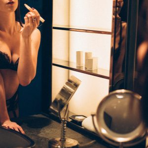 GFE London escort in black lace lingerie applying makeup