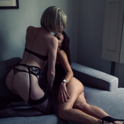 bisexual london escorts Louisa and Rose lounge on a sofa in their lingerie