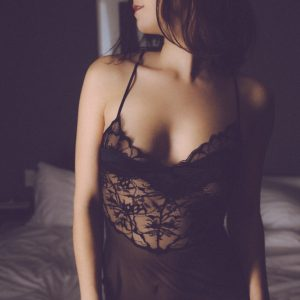 International kinky companion louisa knight poses in a black silk slip, showing off her pert breasts