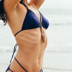 International GFE escort Louisa Knight reclines on the beach in a string bikini