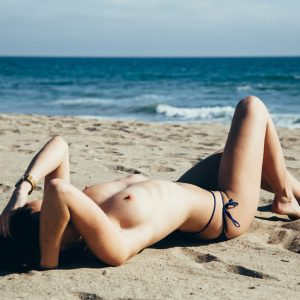 International GFE escort Louisa Knight reclines on the beach in a bikini