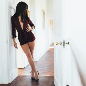 Kinky London escort Louisa Knight in sexy red dress, showing off long legs in heels