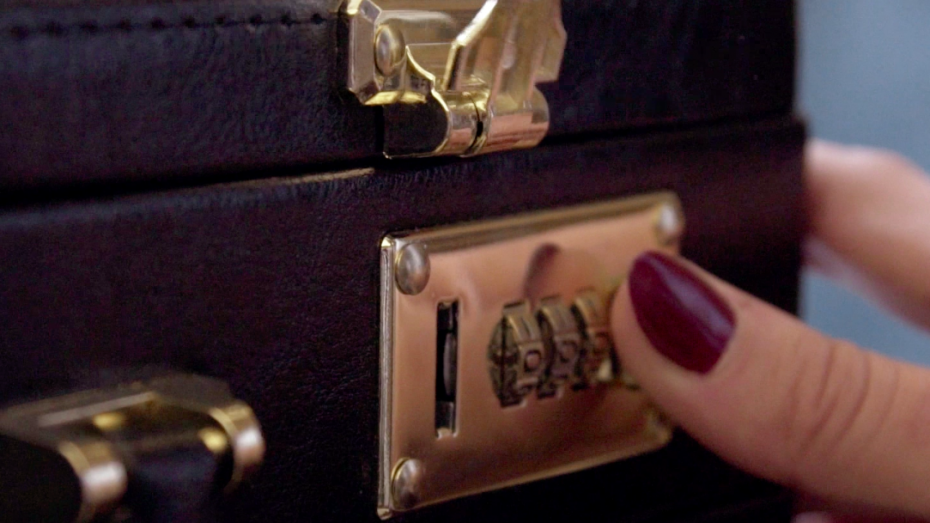 Submissive escort Louisa Knight opens a briefcase with a manicured hand
